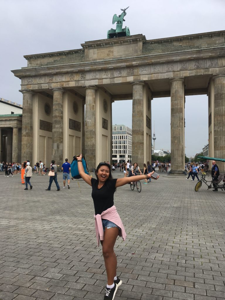 perempuan dengan t-shirt hitam berlatar belakang gerbang brandenburg