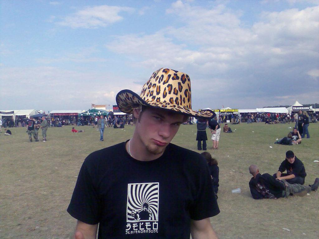 pria muda berbaju hitam dan topi di area konser musik musim panas
