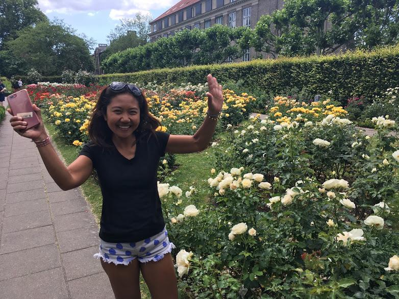 perempuan berkaos hitam tertawa  di taman bunga mawar