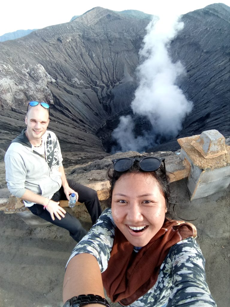 selfie dengan latar kawah bromo yang mengeluarkan asap belerang